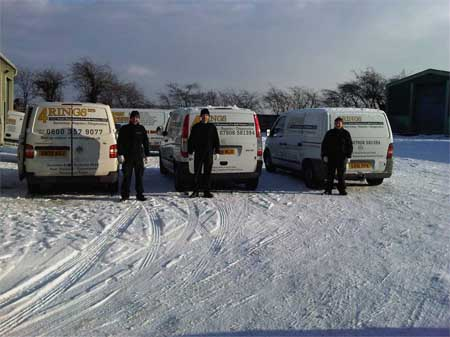 4 Ring's mechanics in behind their vans in the snow